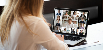 woman sitting in front of her computer, participating in a virtual meeting