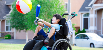 active boy in wheelchair with bat and ball